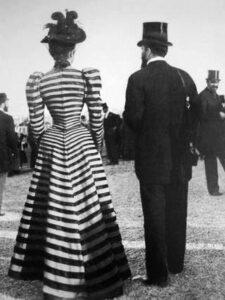 Fotografia czarno biała, wykonana na przełomie XIX i XX wieku. Przedstawia elegancką parę znajdującą się na deptaku. Mężczyzna ubrany w surdut i cylinder stoi u boku kobiety w długiej, wciętej w talii sukni. Dopełnieniem stroju damy jest kapelusz z gustowny piórem. Na drugim planie znajduje się równie elegancko ubrany gentleman.