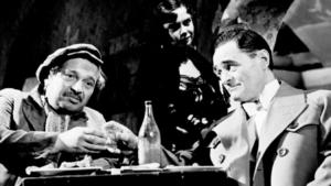 Kadr z komedii obyczajowej pt. Nikodem Dyzma. Reżyseria Jan Rybkowski (1956 r.). Fotografia czarno biała przedstawiająca dwóch mężczyzn pijących alkohol. Sądząc po skromnej zastawie stołowej, libacja odbywa się w podrzędniej knajpie bądź melinie. Mężczyzna z lewej strony to typ niechlujnego pijaczka, człowieka z nizin społecznych. Towarzyszy mu elegancko ubrany kompan. W tle widzimy nieostrą postać kobiecą.