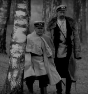 Fotografia przedstawia dwóch żandarmów Carskich idących przez brzozowy las. Niższy z policjantów ubrany jest w białą, służbową pelerynę z pod której wystaje ostrze szabli. Wyższy z funkcjonariuszy ma założony na mundur stary chłopski kożuch. Przedstawiciele prawa wyglądają niechlujnie, sprawiają wrażenie niezainteresowanych służbą. Można określić ich jako ofermy kompanijne.